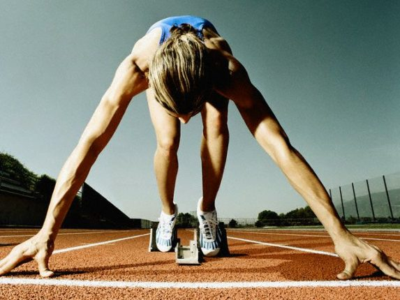 ca. 2003 --- Runner Crouching at Starting Line --- Image by © Randy Faris/CORBIS